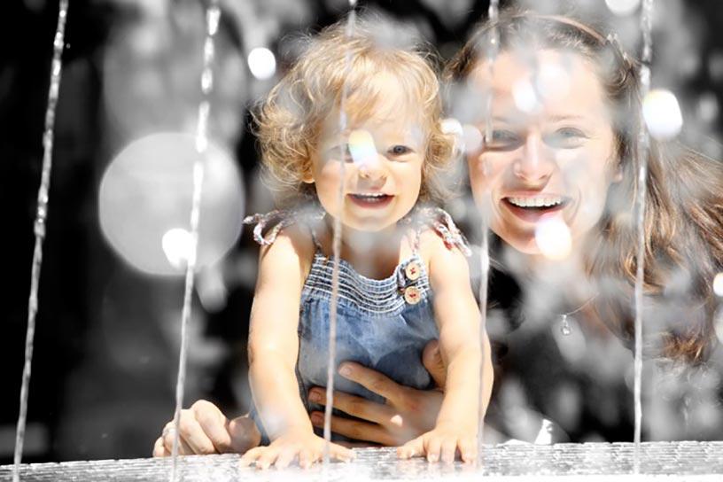 Une mère et sa fille regardent une fontaine