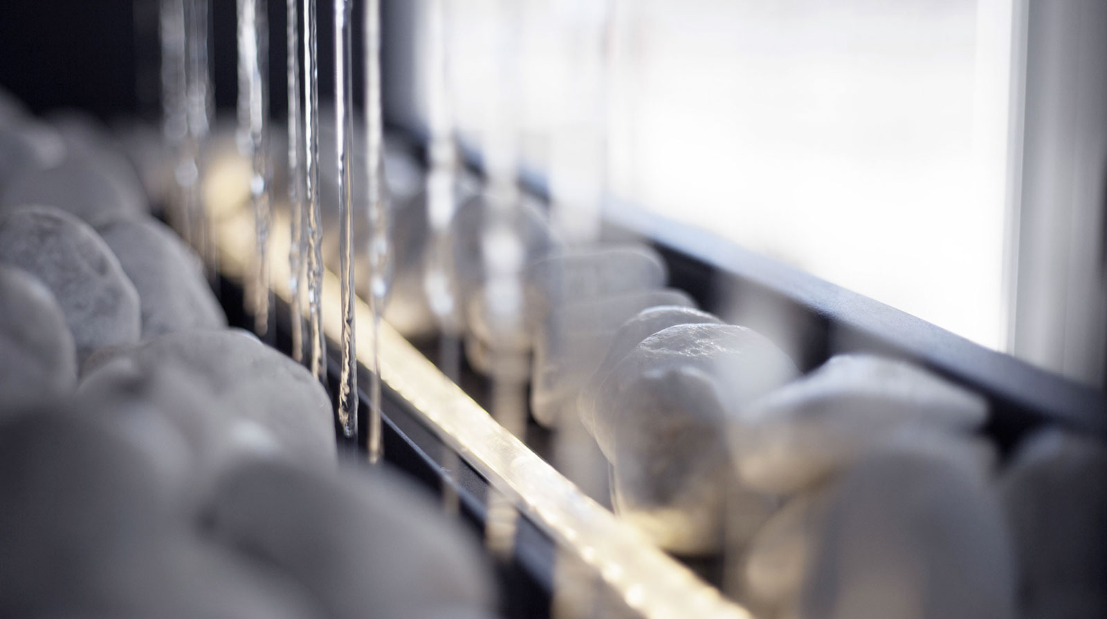 Vue de détail de la fontaine fil d'eau : cailloux blancs sur lesquels coule un mur d'eau
