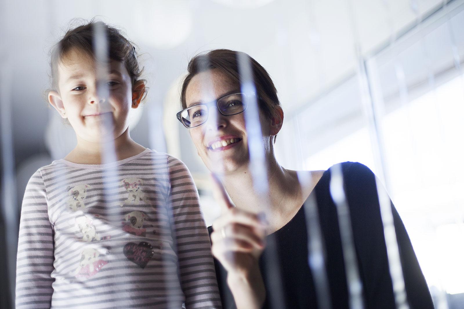 Femme et enfant observent la fontaine Fil d'eau