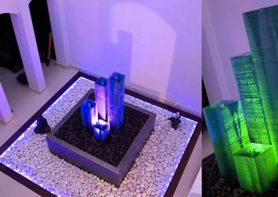 Colonne en verre avec effets de lumière dans un patio